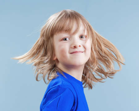 studio portrait of a boy with long blond hair - isolated on blue photo