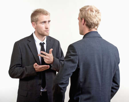 two you businessmen standing, discussing, arguing - isolated on light gray photo