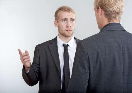 two young businessmen standing, discussing, arguing photo