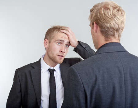 two young businessmen standing, discussing, arguing