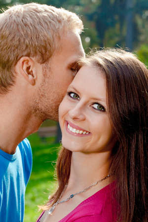 Young Girl Smiling as her Boyfriend Whispers in her Ear. photo