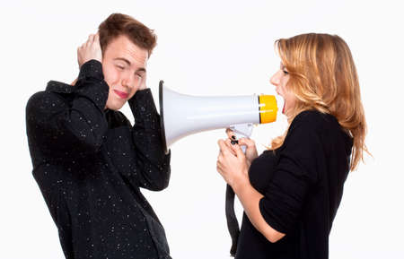 angray girlfriend screaming in megaphone, boyfriend covering his ears photo