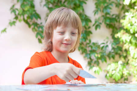 card game: Boy with Blond Hair Playing Cards Outdoors