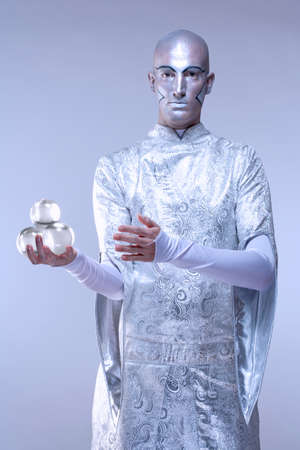 Magician with Glass Balls in Stage Makeup and Costume photo