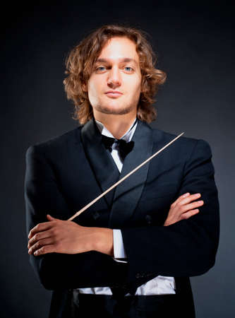 frock coat: Portrait of a Young Conductor Holding a  Baton. Stock Photo