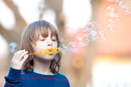 caucasion: Boy with Blond Hair Blowing Bubbles Outdoor