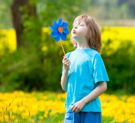 Boy with Pinwheel in a Meadow of Dandelions photo