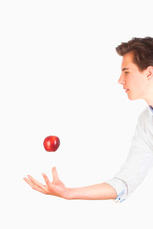 tossing: Young Man Tossing Red Apple in the Air Stock Photo