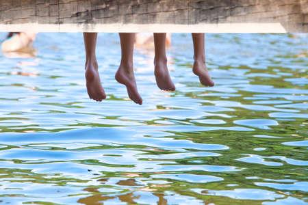 Ragazzi gambe penzoloni giù dal molo di legno sopra acqua