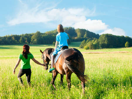 lead sled: Horseback Riding Lessons - Woman Leading a Horse with a Boy in Saddle