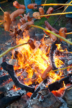 glow stick: People Grilling Sausages over Campfire Outdoors.