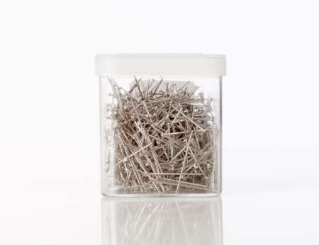 Plastic doos kleine nagels op wit Stockfoto
