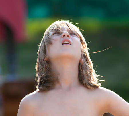 Portrait of a Boy with Blond Hair Looking Up Outdoors Stock Photo