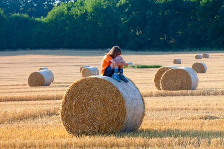 Boy Sitting on a Bale of Hay in Summer