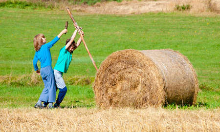 Two Boys Moving Bale of Hay with Stick as a Lever