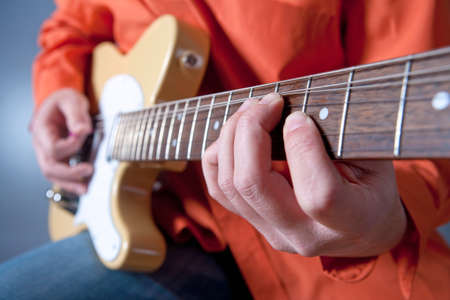 Fingers of a guitar player playing electric guitar.