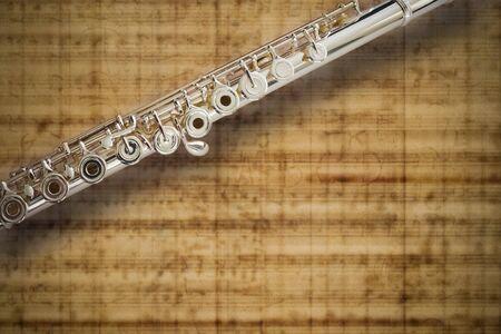 boehm flute: Flauta media conjuntas�lido plata  sobre fondo de hoja de m�sica