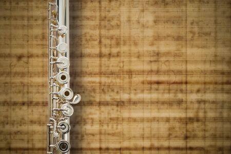 dwarsfluit: Fluit midden Jointeffen zilver  op muziek bladachtergrond  Stockfoto