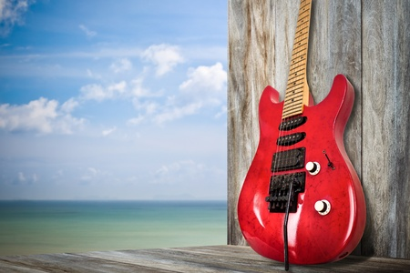 fender stratocaster: Red Old Electric Guitar on a Dock by the Sea