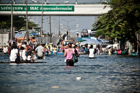 BANGKOK - NOVEMBER 13: A group of people evacuates from the flooded area at Sapan Mai district during the massive flood crisis on November 13, 2011 in Bangkok.  Stock Photo - 11244914