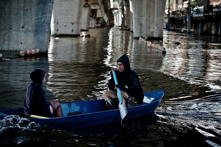 BANGKOK - NOVEMBER 13: An unidentified couple sails a boat on a road in the flooded area at Bang Khen road during the massive flood crisis on November 13, 2011 in Bangkok.