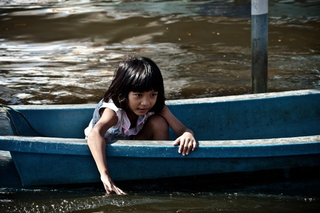 BANGKOK - NOVEMBER 13: An unidentified female child sits on plastic boat in the flooded area at Bang Khen road during the massive flood crisis on November 13, 2011 in Bangkok.