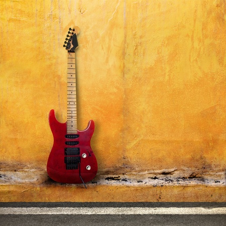 Red Old Guitar on a Grudge Yellow Wall  photo