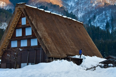 Shirakawago, JAPAN - MARCH 27  Unidentified man plows the snow on the roof from his traditional Gassho-zukuri cottage in the evening on March 27, 2012 in Shirakawago, Japan