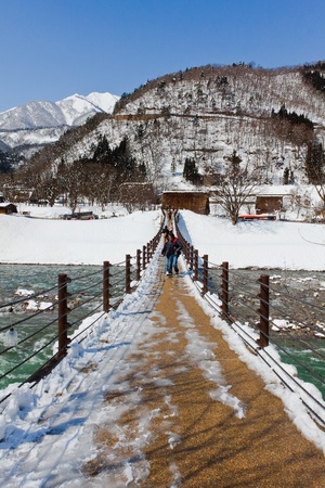 SHIRAKAWA GO, JAPAN - MARCH 27  Unidentified people cross the bridge over Shogawa river to the Ogimachi Village, one of Japan s UNESCO world heritage sites on March 28, 2012 in Shirakawa Go, Japan