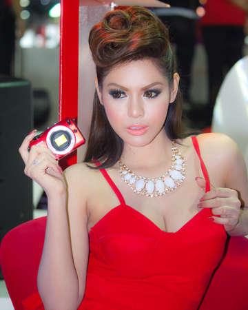 introduces: BANGKOK, THAILAND - DECEMBER 4  Canon EOS M, in Bangkok, Thailand on December, 2012  Unidentified female model introduces Canon EOS M at the Canon Pavillion in THAILAND INTERNATIONAL MOTOR EXPO 2012  Editorial