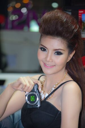 introduces: BANGKOK, THAILAND - DECEMBER 4  Canon EOS M, in Bangkok, Thailand on December, 2012  Unidentified female model introduces Canon EOS M at the Canon Pavillion in THAILAND INTERNATIONAL MOTOR EXPO 2012  Editorial