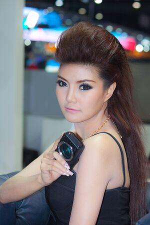 introduces: BANGKOK, THAILAND - DECEMBER 4  Canon EOS M, in Bangkok, Thailand on December, 2012  Unidentified female model introduces Canon EOS M at the Canon pavilion in THAILAND INTERNATIONAL MOTOR EXPO 2012