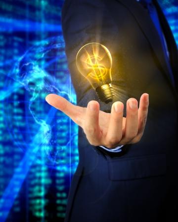 Closeup of a hand of an asian business man with a U S  Dollar lightbulb photo