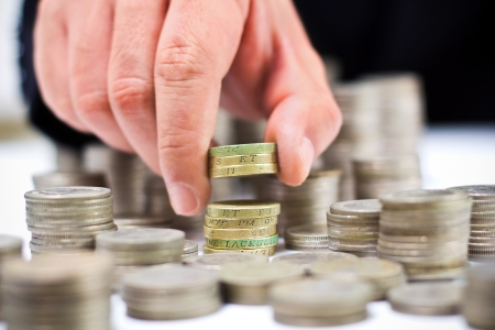 Closeup of stack of british pound coins with a male hand Stock Photo