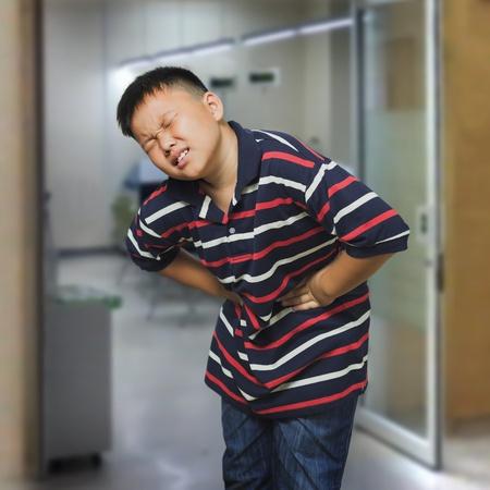 abdominal pain: Giovane ragazzo asiatico con un dolore addominale