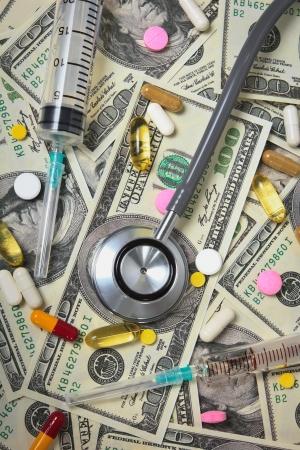doze: Stethoscope with hypodermic syringe and doze of medical tablets on U S  dollar banknotes Stock Photo