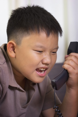 scold: Young asian boy scold at the telephone