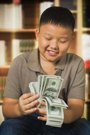 us dollar: Asian boy with U.S . dollar bank notes Stock Photo