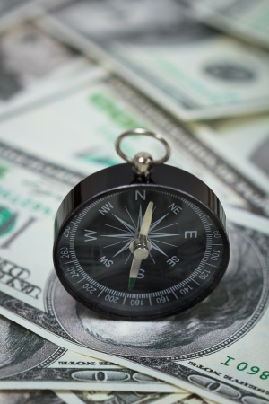 fiscal cliff: Closeup of a compass placed on U S  Dollar banknotes Stock Photo