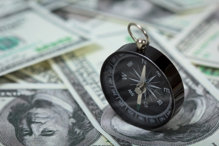 Closeup of a compass placed on U S  Dollar banknotes Stock Photo
