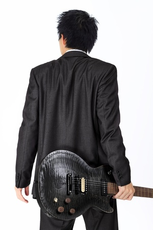 Isolated Asian man with a black electric guitar photo
