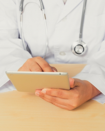 diagnoses: Close up of an Asain female doctor diagnoses by using tablet  Stock Photo