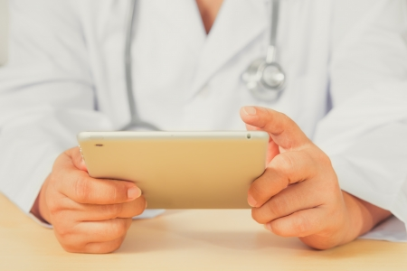 Close up of an Asain female doctor diagnoses by using tablet  photo
