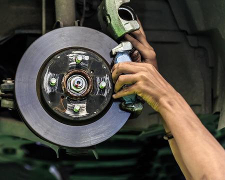 Hände eines Mechanikers installieren Bremsbelag auf einem Auto Scheibenbremse