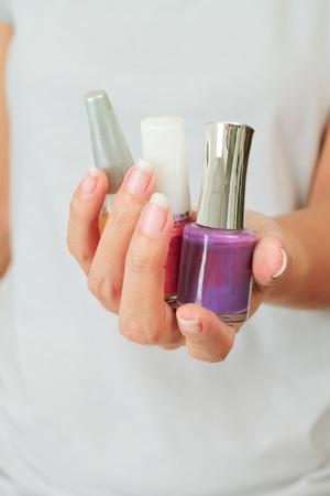 Aislado Mujeres con botellas de barniz de uñas Foto de archivo