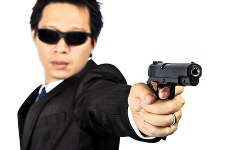 Isolated asian male with a gun on white
