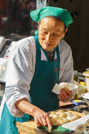 shop keeper: FUKUOKA, JAPAN - NOVEMBER 13: Japanese sweet in Fukuoka, Japan on November 13, 2013. Unidentified female shop keeper sells a plate of japanese sweets in her shop nearby Dazaifu Tenmangu