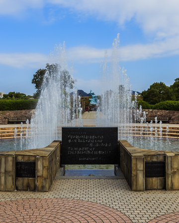 signifies: NAGASAKI, JAPAN - NOVEMBER 14: Nagasaki Peace Park in Nagasaki, Japan on November 14, 2013. Fountain of peace sprays water in shape of doves wings, signifies pity on people who died begging for water in the war in 1945