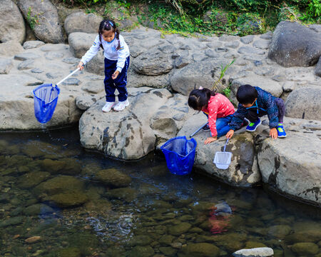 learning process: NAGASAKI, JAPAN - NOVEMBER 14  Nakashima River in Nagasaki, Japan on November 14, 2013  Teachers take smalls students to collect garbage from the river as an activity for environmental learning process