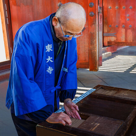 todaiji: NARA, JAPAN - NOVEMBER 16  Japanese Monk in Nara, Japan on November 16, 2013  Arranges joss sticks for people who travel to pay respect the temple at Chumon Gate in Todaiji Temple